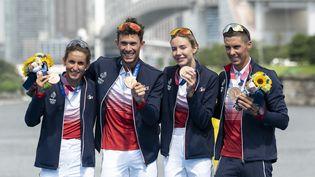 Leonie Periault, Dorian Coninx, Cassandre Beaugrand et Vincent Luisposent avec leur médaille de bronze après l'épreuve de relais mixte en triathlon, le 31 juillet à Tokyo. (CHARLY TRIBALLEAU / AFP)