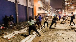 Des manifestants s'enfuient après que des policiers ont ouvert le feuavec des balles en caoutchouc dans le quartier de Jeppestown, à Johannesburg, le 11 juillet 2021. Plusieurs magasins y ont été pillés et des voitures incendiées. (LUCA SOLA / AFP)