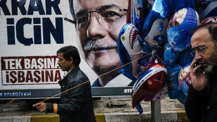 29 octobre 2015. Un vendeur de ballons devant un portrait du Premier ministre turc AhmetDavutoglu, quelques jours avant les législatives du 1er novembre 2015. (DIMITAR DILKOFF / AFP)