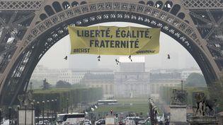 Des militants de Greenpeace déploient une banderole contre le Front national sur la tour Eiffel, vendredi 5 mai 2017 à Paris. (JACQUES DEMARTHON / AFP)