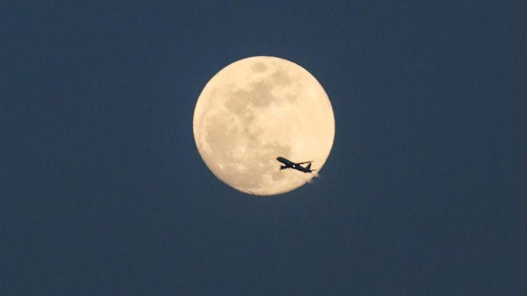 Un avion passe devant la Lune dans le ciel de Manhattan à New York, le 28 février 2018. (WILLIAM VOLCOV / BRAZIL PHOTO PRESS)
