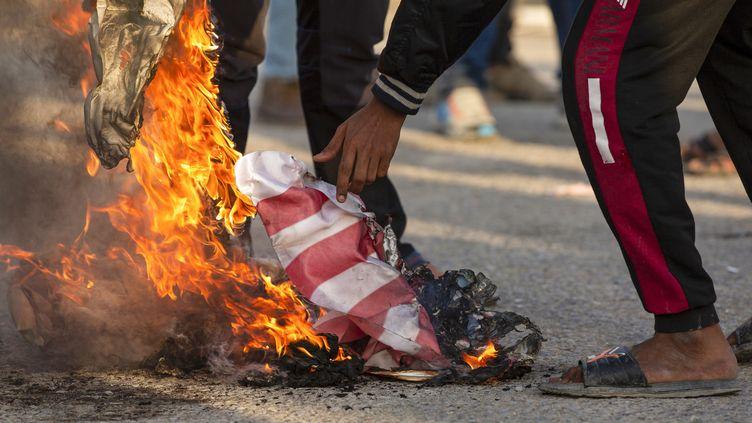 Le drapeau américain brûlé par des Irakiens durant une manifestation, le 30 décembre 2019 à Basra (Irak). (HUSSEIN FALEH / AFP)