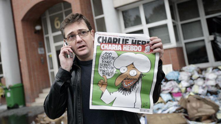 """Le dessinateur Charb brandit un exemplaire de """"Charlie Hebdo"""", rebaptisé """"Charia Hebdo"""", après l'incendie des locaux du magazine, à Paris, le 2 novembre 2011. (ALEXANDER KLEIN / AFP)"""