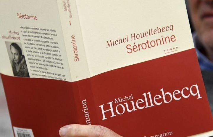 """Un homme lit """"Sérotonine"""" dans une librairie parisienne  (BERTRAND GUAY / AFP)"""