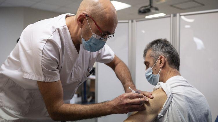Un soignant reçoit une dose d'un vaccin contre le Covid-19, le 12 janvier 2021 à Annonay (Ardèche). (BASTIEN DOUDAINE / HANS LUCAS)