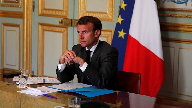 Emmanuel Macron dans son bureau de l'Elysée, écoutant une intervention d'Angela Merkel lors d'une conférence vidéo commune, le 18 mai 2020. (POOL NEW / REUTERS)