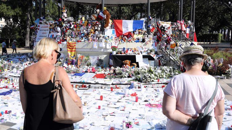 Deux personnes se recueillent devant un mémorial improvisé en souvenir des victimes de l'attentat de Nice, le 19 juillet 2016 à Nice. (VALERY HACHE / AFP)