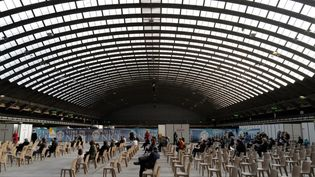 Des personnes patientent au sein du centre de vaccination contre le Covid-19 installé au Palais des congrès et des expositions de Nice, le 9 avril 2021. (VALERY HACHE / AFP)