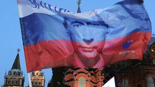 Un drapeau russe à l'effigie de Vladimir Poutine flotte sur la place du Manège, dans le centre deMoscou, le 5 mars 2012. Déjà président entre 1999 et 2008, l'ancien officier du KGB a été élu chef de l'Etat dès le premier tourla veille, après un intérim de quatre ans en tant que Premier ministre de Dmitri Medvedev. (ALEXANDER NEMENOV / AFP)