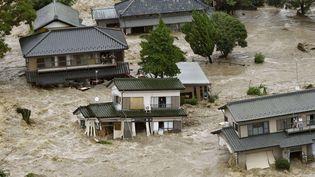 Réfugiés sur le balcon de leurs habitations, des habitants de Joso (Japon) appellent à l'aide, jeudi 10 septembre 2015. (KYODO NEWS / AP / SIPA)