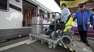 Une personne handicapée monte dans un train Corail Intercités à l'aide d'une plateforme, le 23 mars 2009 à la gare de Caen (Calvados), lors de l'inauguration de la première voiture adaptée au voyage de personnes en fauteuil roulant et à mobilité réduite. (MYCHELE DANIAU / AFP)