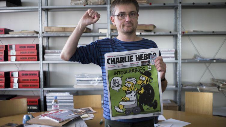 """Le dessinateur Charb pose avec la une d'un numéro de """"Charlie Hebdo"""", le 19 septembre 2012 dans les locaux du journal à Paris. (FRED DUFOUR / AFP)"""
