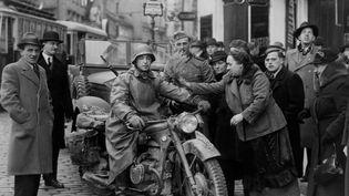 Le 15 mars 1938, un soldat allemand se voit offrir des fleurs dans les rues de Vienne. (STRINGER / FRANCE PRESSE VOIR)