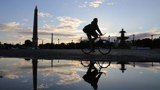 Un cycliste traverse la place de la Concorde, au coucher du soleil, le 14 septembre 2015 à Paris. (LUDOVIC MARIN / AFP)