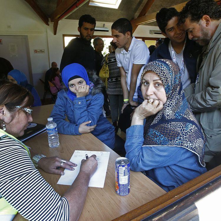 Des réfugiées s'enregistrent auprès des bénévoles du Secours populaire, à leur arrivée au centre d'accueil de Cergy-Pontoise (Val d'Oise), le 9 septembre 2015. (JACKY NAEGELEN / REUTERS)
