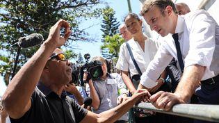 Emmanuel Macron échange avec un habitant de Saint-Denis, le 24 octobre 2019, lors de sa visite sur l'île de La Réunion. (RICHARD BOUHET / AFP)