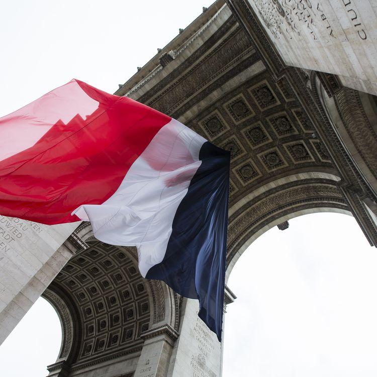 Un drapeau tricolore géant sous l'Arc de triomphe, à Paris, le 8 mai 2015, pour les commémorations du 70e anniversaire de la capitulation de l'Allemagne nazie. (IAN LANGSDON / AFP)