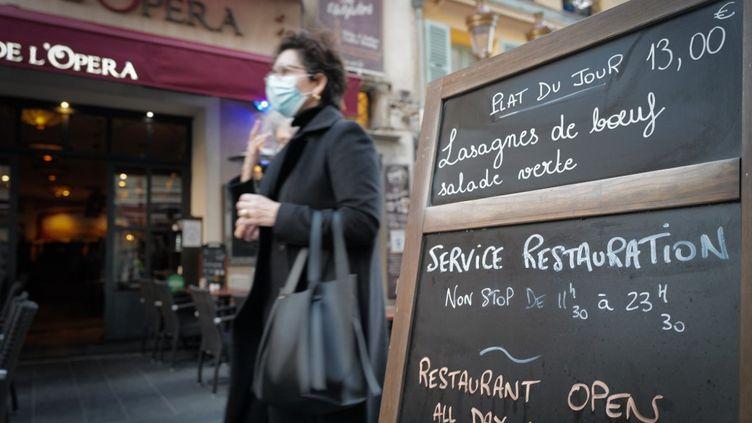 Une femme passe devant un restaurant, à Nice (Alpes-Maritimes), le 22 octobre 2020. (ARIE BOTBOL / HANS LUCAS / AFP)
