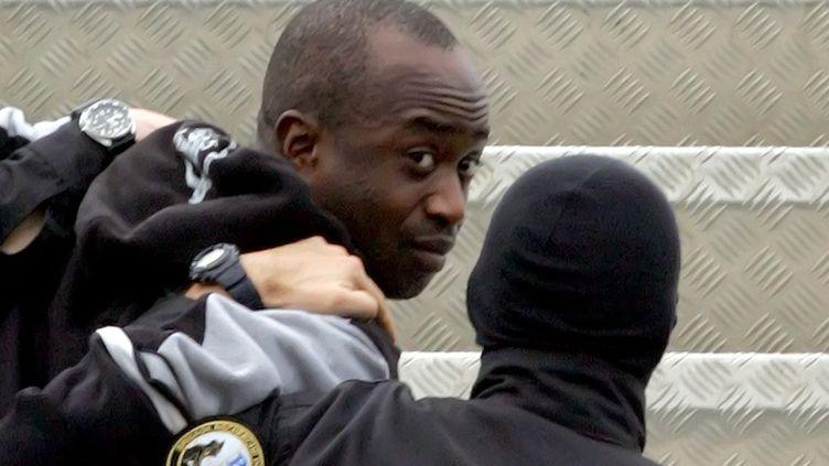 Youssouf Fofana est escorté par deux policiers pour le ramener à Paris en avion,le 4 mars 2006 à Abidjan (Côte-d'Ivoire). (ISSOUF SANOGO / AFP)
