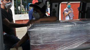 Des proches d'une personne emportée par le Covid-19 se tiennent près de son cercueil pour ses obsèques, le 23 avril 2020 àGuayaquil (Equateur). (JOSE SANCHEZ / AFP)