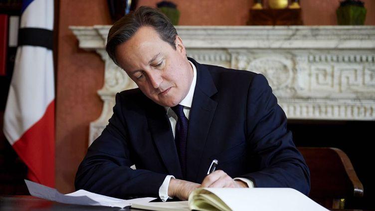 «Nous sommes solidaires avec vous», «Nous sommes tous ensemble», écrit le Premier ministre britannique, en français dans le texte, sur les pages du registre de condoléances, en hommage aux victimes des attentats de Paris le 13 novembre. David Cameron a aussi décidé d'assister au match amical Angleterre-France le 17 au soir, où il est prévu une minute de silence et le chant de l'hymne national français, La Marseillaise. (Niklas HALLE'N / AFP PHOTO )