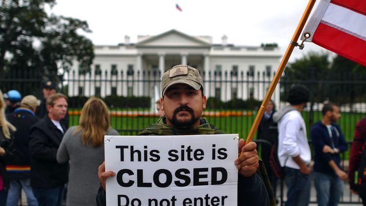 """Un manifestant tient une pancarte """"Ce site est fermé. Ne pas entrer"""", pour demander la fin du """"shutdown"""", le 13 octobre 2013, devant la Maison Blanche, à Washington. (JEWEL SAMAD / AFP)"""