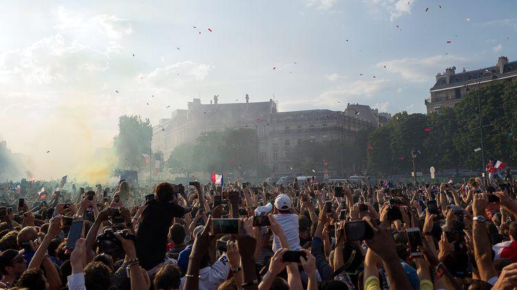 La foulesur les Champs-Elysées, à Paris, pour voir passer le bus des Bleus, lundi 16 juillet 2018. (JPNVHB / MAXPPP)