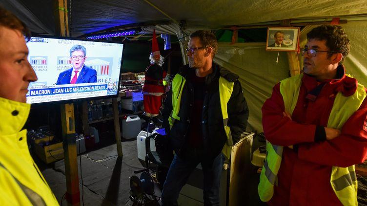 """Des """"gilets jaunes"""" écoutent la réaction de Jean-Luc Mélenchon à l'allocution télévisée d'Emmanuel Macron, le 10 décembre 2018. (JEAN-FRANCOIS MONIER / AFP)"""