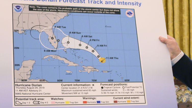 Le président américain, Donald Trump, montre une carte de la trajectoire initialement prévue de l'ouragan Dorian, agrémentée d'un trait tracé au crayon noir, le 4 septembre 2019, à la Maison Blanche. (JIM WATSON / AFP)