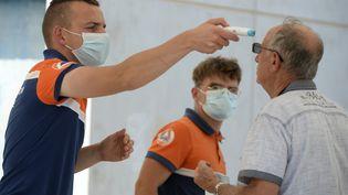 Un sauveteur de la protection civile prend la température d'un homme avant de subir un test COVID-19, à Laval, dans l'ouest de la France, le 17 juillet 2020. (JEAN-FRANCOIS MONIER / AFP)