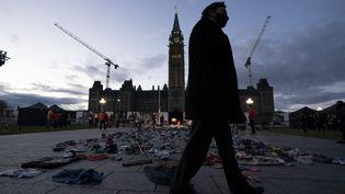 Le juge en chef de la Cour suprême Richard Wagner passe devant des chaussures laissées sur la colline du Parlement, à la veille de la première Journée nationale de vérité et de réconciliation, mercredi 29 septembre 2021 à Ottawa au Canada. (ADRIAN WYLD / MAXPPP)