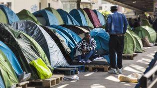 Deux migrants discutent dans un camps installé sous le métro La Chapelle, à Paris, le 1er juin 2015. (GEOFFROY VAN DER HASSELT / ANADOLU AGENCY / AFP)