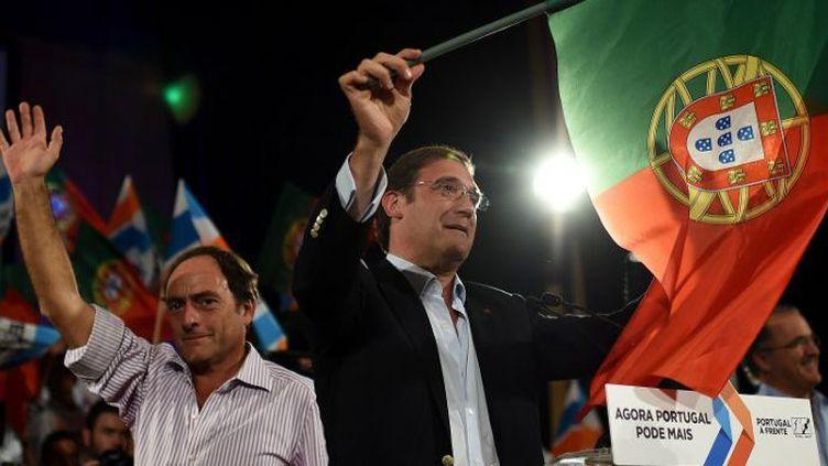 Pedro Passos Coelho, Premier ministre du Portugal (à droite), avec le drapeau national à la main, en campagne électorale le 27 septembre 2015. Le Parti social démocrate (à ne pas confondre avec le Parti socialiste) est au pouvoir avec les conservateurs. Cette alliance, Portugal a frente (Portugal en avant) brigue un nouveau mandat. (FRANCISCO LEONG / AFP)