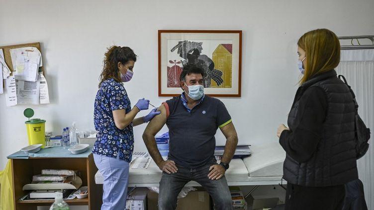 Un homme se fait vacciner, le 23 avril 2021sur l'île d'Elafonissos (Grèce). (ARIS MESSINIS / AFP)