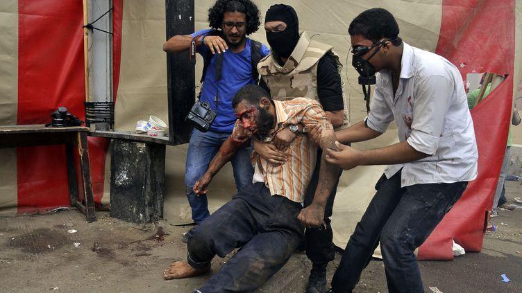 Un partisan de Mohamed Morsi, blessé, est évacué de la place Nahda, au Caire (Egypte), mercredi 14 août 2013. (ENGY IMAD / AFP)