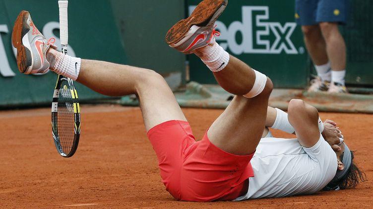 Rafael Nadal s'effondre après avoir remporté la balle de match face à David Ferrer, le 9 juin 2013, en finale de Roland-Garros à Paris. (PATRICK KOVARIK / AFP)