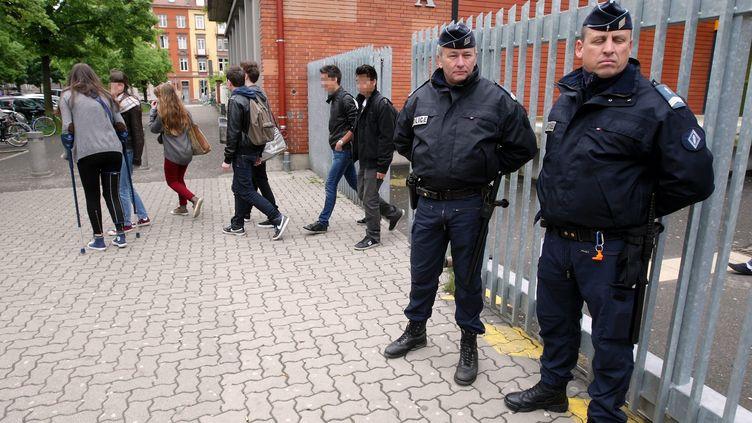 Des policiers surveillent l'entrée d'un lycée de Strasbourg (Bas-Rhin), le 21 mai 2013, après que des menaces de tuerie ont été émises sur internet. (MAXPPP)