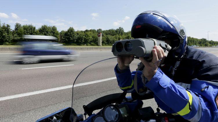 Un gendarme contrôle la vitesse des automobilistes sur l'A36, à Beaune (Côte d'Or), le 6 juillet 2013. (KENZO TRIBOUILLARD / AFP)