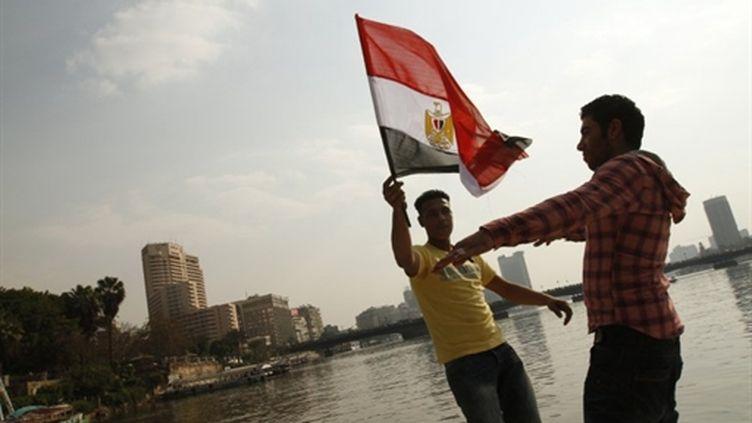 De jeunes égyptiens brandissent le drapeau national trois jours après la démission d'Hosni Moubarak (14/02/2011) (AFP - Mohammmed Abed)