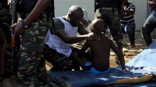 Un soldat ivoirien réconforte un enfant après l'attaque contre trois hôtels dans la station balnéaire de Grand-Bassam (Côte d'Ivoire), le 13 mars 2016. (JOE PENNEY / REUTERS)