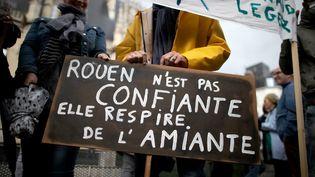 """Une pancarte """"Rouen n'est pas confiante, elle respire de l'amiante"""" tenue par un manifestant à Rouen (Seine-Maritime), le 1er octobre 2019. (LOU BENOIST / AFP)"""