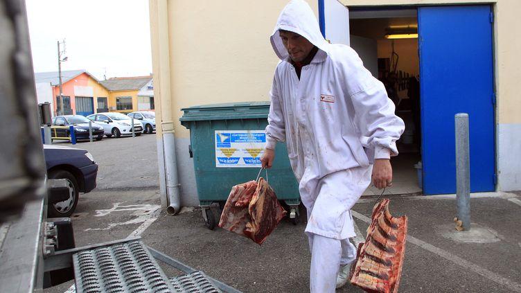 Un employé réquisitionné transporte des viandes suspectes, le 16 décembre à Narbonne (Aude). (RAYMOND ROIG / AFP)