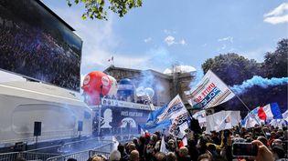 Des policiers brandissent des drapeaux de syndicats de police et allument des bombes fumigènes alors qu'ils se rassemblent devant l'Assemblée nationale à Paris, le 19 mai 2021. (THOMAS COEX / AFP)