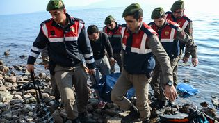 Des gendarmes turques récupèrent les corps de victimes d'un naufage en mer Egée, samedi 30 janvier 2016. (OZAN KOSE / AFP)