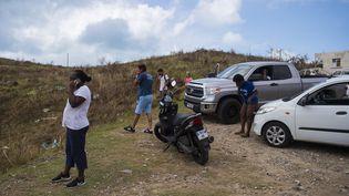Des habitants de l'île de Saint-Martin tentent de téléphoner, près d'une antenne relais, le 7 septembre 2017. (LIONEL CHAMOISEAU / AFP)