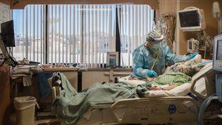 Une infirmière au chevet d'une patiente hospitalisée après une contamination au Covid-19, lundi 11 janvier 2021 à Apple Valley, en Californie (Etats-Unis). (ARIANA DREHSLER / AFP)