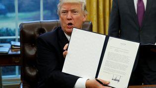 Le président américain Donald Trump a signé, lundi 23 janvier 2017, à la Maison Blanche,un document mettant fin à la participation des Etats-Unis au traité de libre-échange transpacifique (TPP). (KEVIN LAMARQUE / REUTERS)