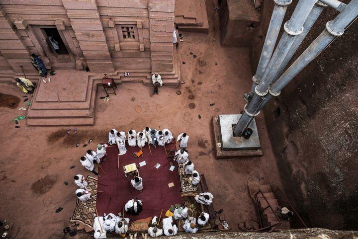 Les dévots de l'église orthodoxe prient à proximité d'un pilier de soutien.  (EDUARDO SOTERAS / AFP)