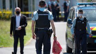 Un gendarme français apporte des fleurs après l'attaque au couteau d'une policière municipale, le 28 mai 2021, à La Chapelle-sur-Erdre, près de Nantes. (LOIC VENANCE / AFP)