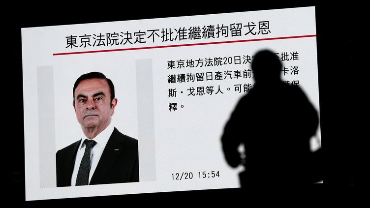 Un piéton regarde un programme d'informations consacré àCarlos Ghosn à Tokyo (Japon), le 20 novembre 2018. (BEHROUZ MEHRI / AFP)